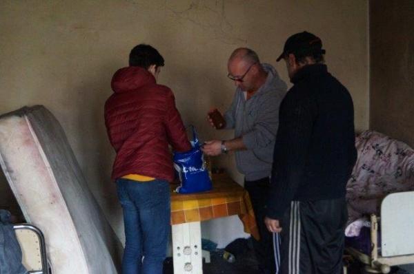 Un preot împarte ajutoare alimentare săracilor din Carei